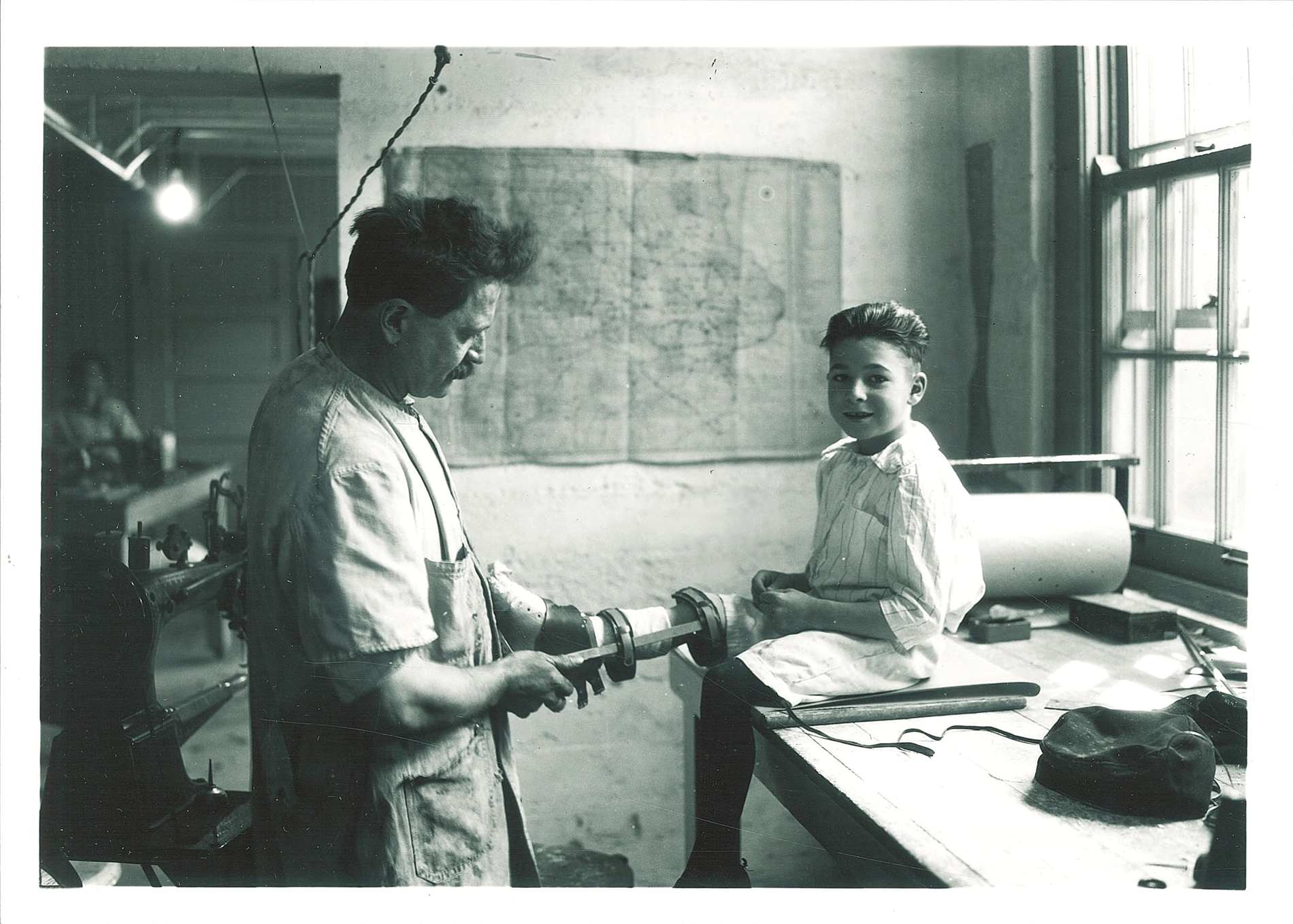 P.G. Mott constructs a brace for a child in the Children's Hospital brace shop, May 1920