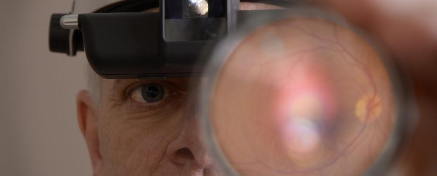 image of doctor examine an eye through a magnifer