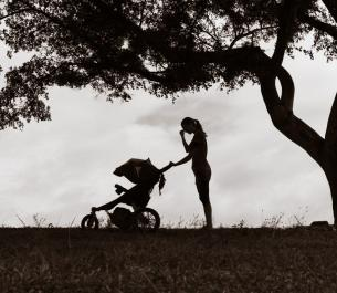 silhouette of woman pushing a baby stroller