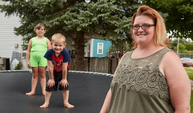 a woman with her kids on a trampoline